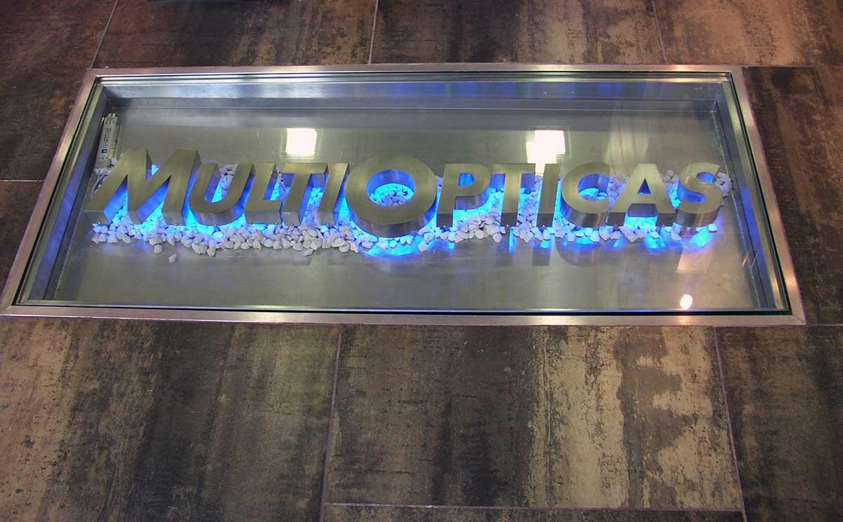 Letras corpóreas con luz en el suelo - Multiopticas